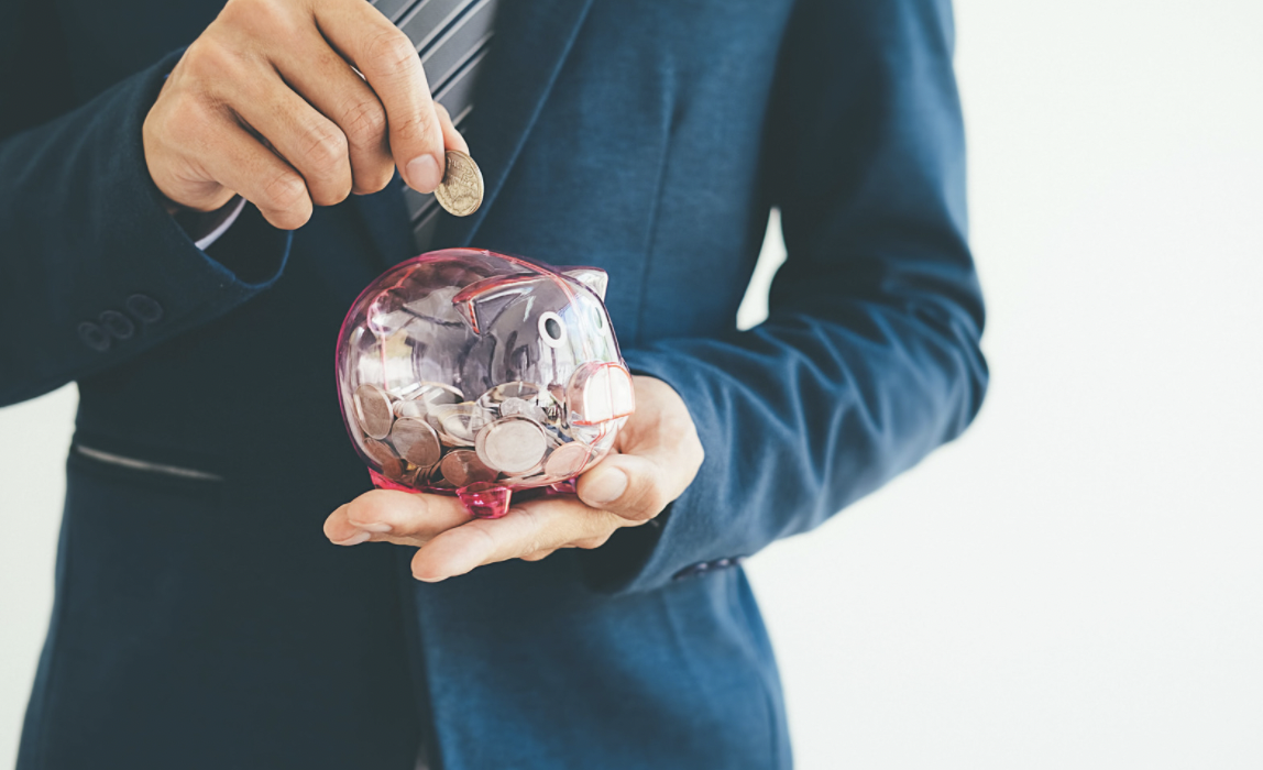 man in suit putting coins in glass piggy bank